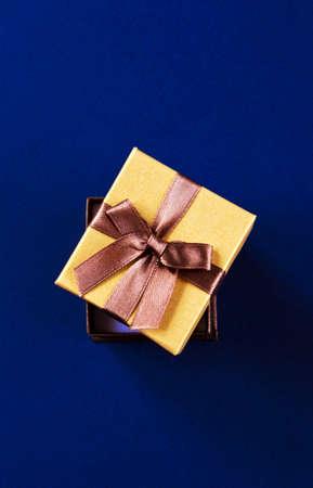 Open golden gift box on blue background