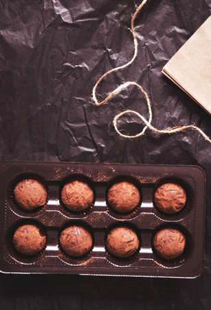 Gift box with dark cocoa truffles on black paper background