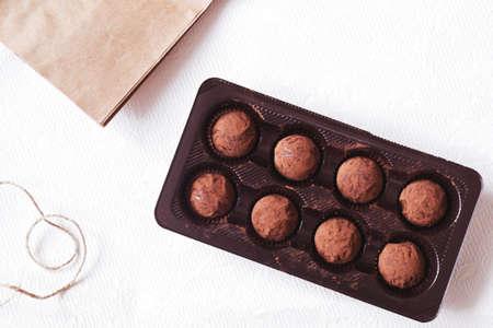 Dark cocoa truffles in the box on white background