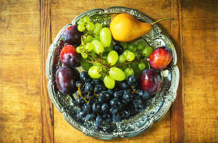 Fresh fruit assortment on a silver tray on a wooden background. Ripe grapes, plums and pear