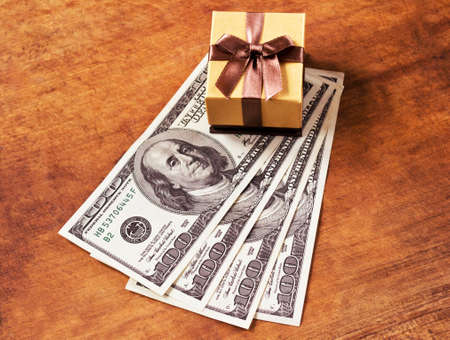 Golden gift box with jewelry and four hundred dollars on wooden board
