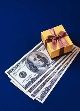 Beautiful golden gift box with jewelry and four hundred dollars on a blue board Фото со стока