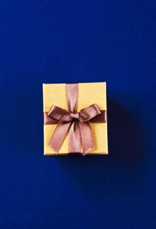 Beautiful golden gift box on blue background Фото со стока