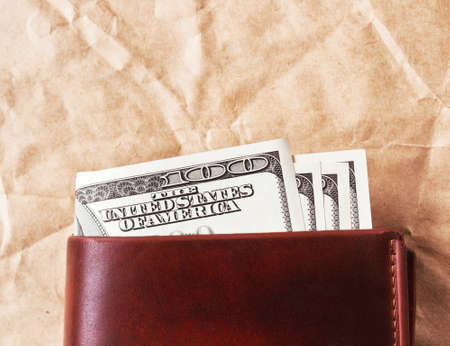 Brown leather wallet with US dollars on paper Фото со стока