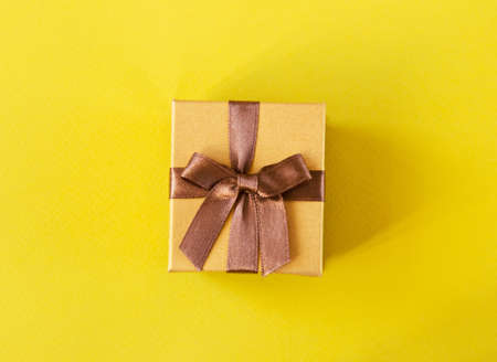 Golden gift box on yellow background