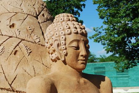 Sand sculpture of Buddha meditating