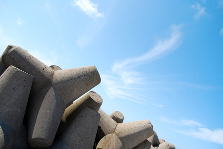 Concrete jetty surrounded by rocks - clear blue sky