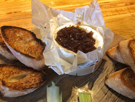 Typical UKs starter - Baked Camembert cheese with onion chutney Imagens