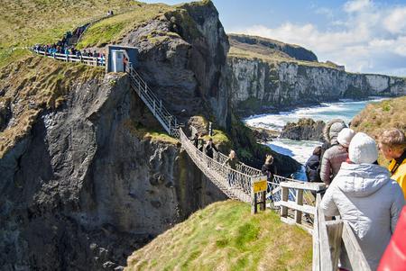 Ballintoy, Reino Unido - 2 de mayo de 2016: Puente de cuerda de Carrick-a-Rede, un destino turístico popular en Irlanda del Norte. Turistas pasando el puente.