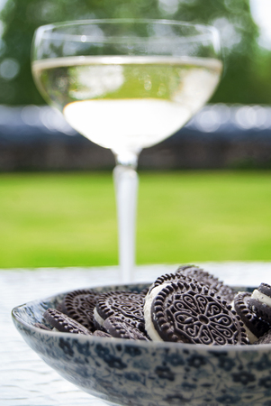 Delicious cookies with cream filling and a glass of sparkling wine