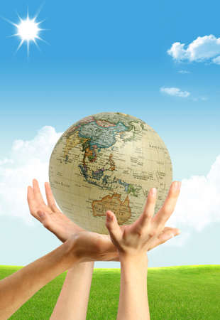 Three hands and a globe on the blue shining sky background Stock Photo - 5099080
