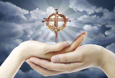 sanctity: Una bella combinazione con le mani e una croce sullo sfondo del cielo Archivio Fotografico