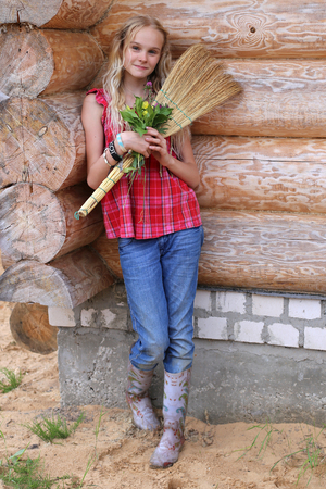 country lifestyle: young girl with broom and flowers