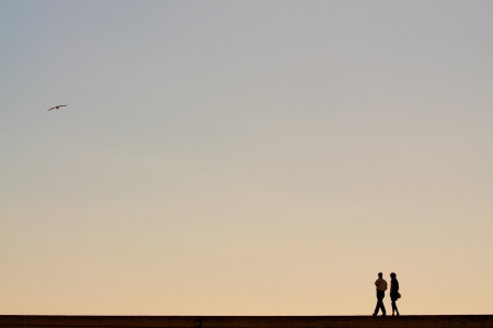 Couple walking at sunset in a harbor photo