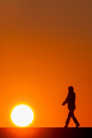 People walking at sunset with the sun next Stock Photo - 19293625