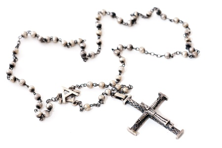 Old silver rosary on white background photo