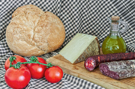 Still life of cheese, salami, tomatoes, bread and sausage photo
