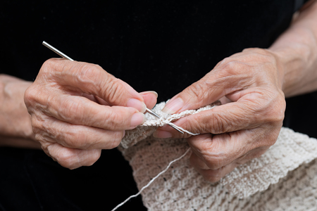 Detail of the hands of an elderly person crocheting photo