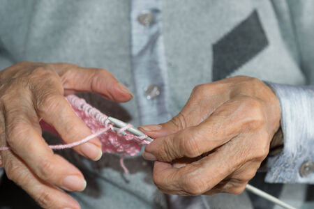 purl: Hands of elderly person doing Knitting