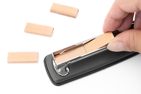 Hand putting staples in a stapler