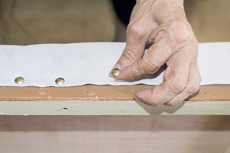 upholsterer: Details elderly person  renewal of the upholstery of a chair