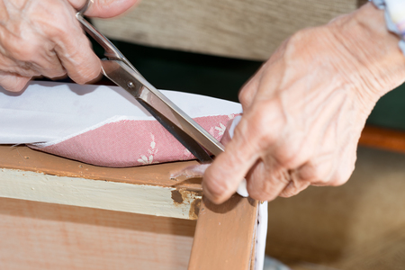 sofa furniture: Details elderly person  renewal of the upholstery of a chair
