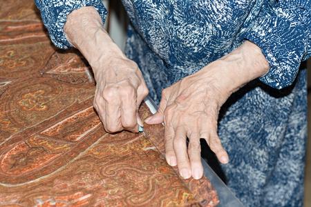 dressmaker: Details of a dressmaker weaving a cushion