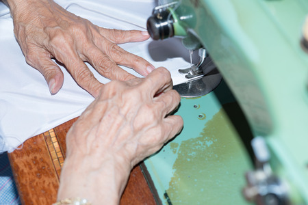 needlewoman: Details of an old woman with a sewing machine