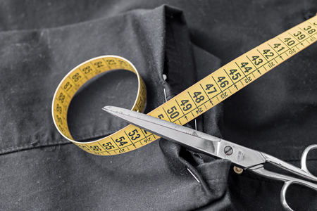 Trousers, scissors and measuring tape in a tailor shop