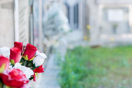 memorial cross: Detalle de un ramo de flores en un cementerio