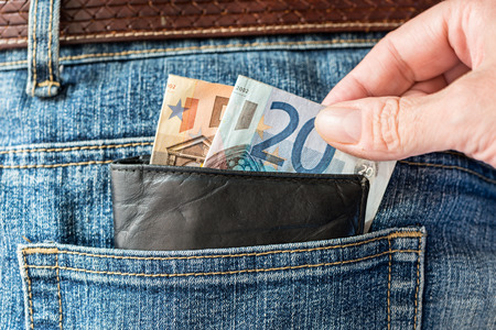 Thief taking money from his pants pocket
