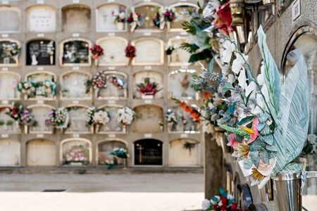 Barcelona, Spain - April 30, 2019. - Details of tombs and burial niches in formation of several floors adorned with typical flowers of traditional Spanish cemeteries, in the local cemetery of the city of Mataro. Stock Photo
