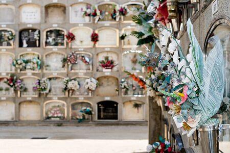 Barcelona, Spanien - 30. April 2019. - Details zu Gräbern und Grabnischen in mehreren Etagen, die mit typischen Blumen traditioneller spanischer Friedhöfe geschmückt sind, auf dem örtlichen Friedhof der Stadt Mataro. Standard-Bild