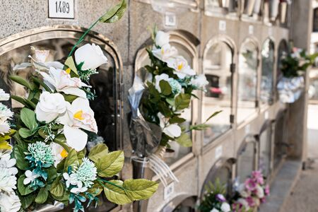 Barcelona, Spain - April 30, 2019. - Details of tombs and burial niches in formation of several floors adorned with typical flowers of traditional Spanish cemeteries, in the local cemetery of the city of Mataro.