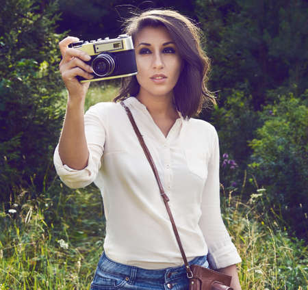 dense forest: Fashion street photo of elegant lady in  in a dense forest with film camera