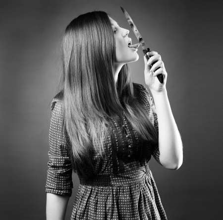 young knife: Bbeautiful young girl holding a knife on her lips in a dress