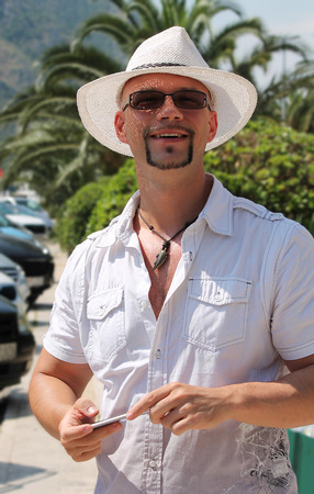 cheerfully: Handsome man in white shirt and hat smiling cheerfully. Stock Photo