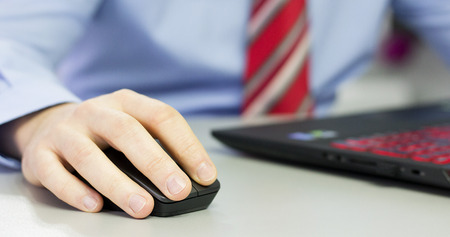 Hands leaning and clicking on office mouse. Stock Photo