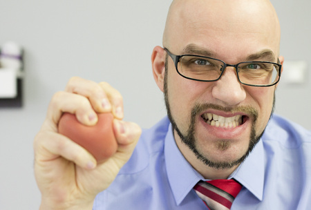 Boss squeezing stress ball in the office - dissapointed manager. Stock Photo