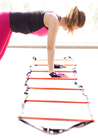 Woman using agility ladder in the fitness class.