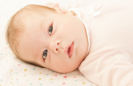 portait: Close-up portait of a baby girl in her comfy bed. Stock Photo