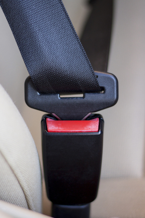 lux: Close-up view of fastened seatbelts inside a car.
