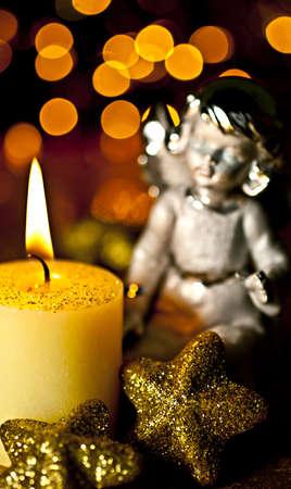 Christmas Angel staring at a burning candle photo