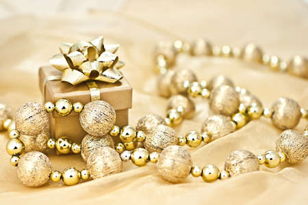 The gold background gold gift box with a string of Christmas ornamental ball. photo