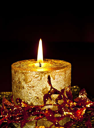 Christmas Decor, a burning candle with glossy leaves on a dark background. photo