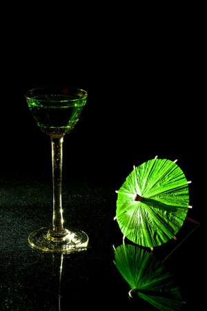 verm�: Sobre un fondo negro con vaso de coctel verde Vermut y una sombrilla verde.