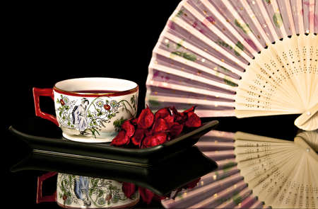An antique teacup with a design. Rear trunnions fan in the background. Stock Photo - 8496430