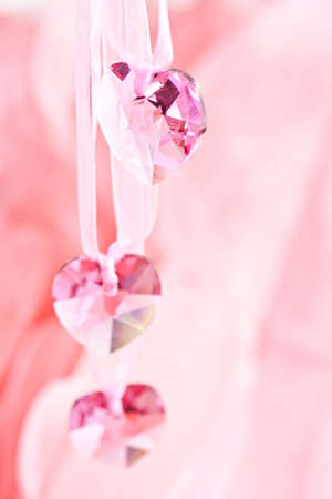 Three crystal hearts on a pink background. photo