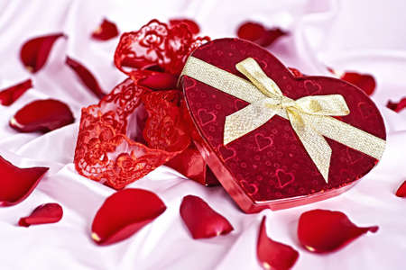 Sobre un fondo de color rosado regalo cuadro de corazón en forma de ropa interior de mujeres, el fondo dispersos pétalos de rosas. Foto de archivo - 8575387