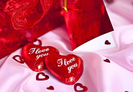 Sobre un fondo de color rosado sorpresa regalo, dos corazón de chocolate en el formulario que te amo, dice. Foto de archivo - 8575378